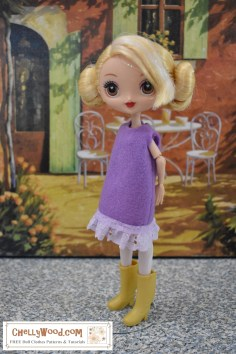 The image shows a Kuu Kuu Harajuku G doll wearing a purple felt dress with eyelet lace trim. Please go to ChellyWood.com for the free printable PDF sewing pattern and easy-to-sew tutorial video that will show you how to make this dress (great for beginners and kids learning to sew)! Please click on the link in the caption to navigate to the right page for this pattern and tutorial.