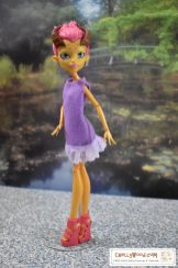 The image shows a Monster High Gilda Goldstag doll wearing a purple felt dress with eyelet lace trim. Please go to ChellyWood.com for the free printable PDF sewing pattern and easy-to-sew tutorial video that will show you how to make this dress (great for beginners and kids learning to sew)! Please click on the link in the caption to navigate to the right page for this pattern and tutorial.