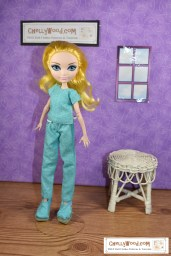 In a purple room with a window, we see an Ever After High doll (same size as a Monster High doll) wearing what appears to be medical scrubs: a pair of pull-on pants with a short-sleeved shirt and a matching pair of Toms-style shoes. Click on the link in the caption, and it will take you to a page where you can download and print all the free printable sewing patterns for making these doll clothes, along with links to tutorial videos that show you how to make this outfit.