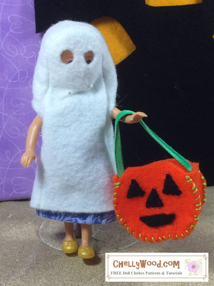 A tiny Chelsea doll or a similar-sized doll is going trick-or-treating for Halloween. She wears a little felt ghost costume with they eyes cut out. She carries a pumpkin-shaped candy basket. She appears to be wearing her ghost costume over a dress of blue printed fabric. Click on the link in the caption, and it will take you to a page where you can download and print all the free printable sewing patterns for making these doll clothes, along with links to tutorial videos that show you how to make this outfit.