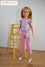 The image shows Mattel's Stacie doll (Barbie's little sister) wearing a pair of capri pants and a short-sleeved cotton shirt. She stands beside a ladder in front of a bare white wall, like she's about to start painting the wall. The free printable sewing patterns and tutorial instructional videos that tell you how to make this outfit for your Stacie doll can be found at the link found in the caption.