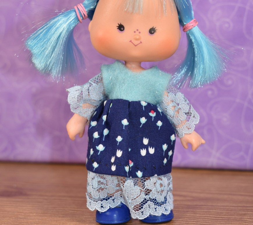 In this photo, we see a BlueBerry Muffin doll from the vintage Strawberry Shortcake collection of dolls modeling a dress that's relatively easy to sew. The dress is made of blue felt, blue lace, and blue cotton with a teeny-tiny floral print in miniature. Click on the link in the caption, and it will take you to a page where you can download and print all the free printable sewing patterns for making these doll clothes, along with links to tutorial videos that show you how to make this outfit.