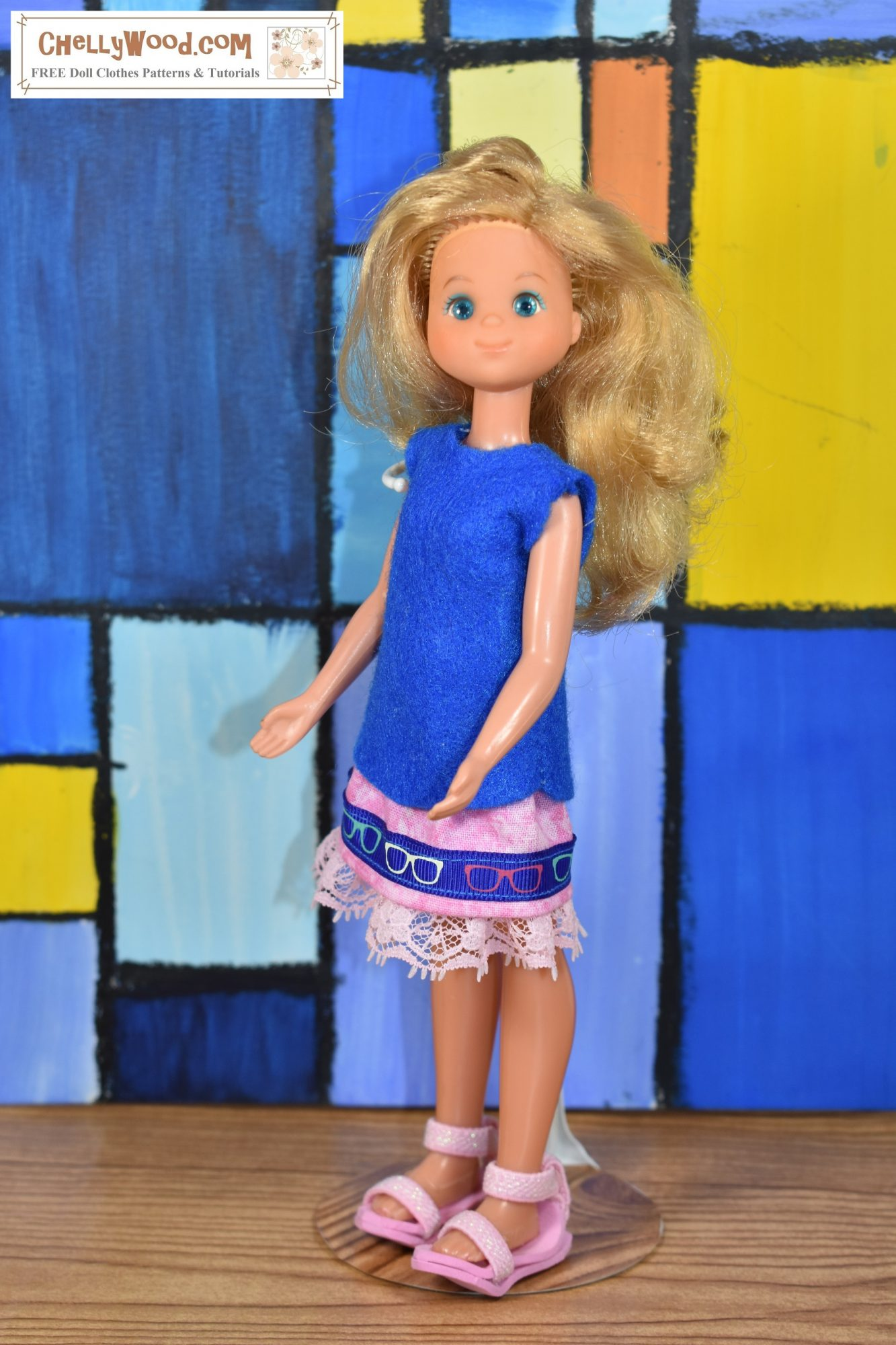 """In this image, a Sunshine Family vintage """"mom"""" doll wears a blue felt handmade shirt and a pink skirt trimmed in ribbon and lace. The doll stands before what appears to be a stained glass style piece of painted artwork. If you'd like to make this outfit for your Sunshine Family doll, please click on the link in the caption that accompanies the image."""