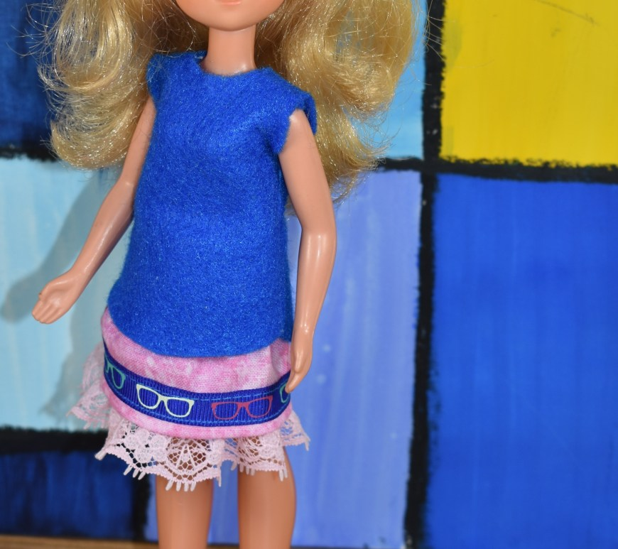 The image shows a vintage Sunshine Family mom / mother doll wearing handmade doll clothes. Her shirt or sleeveless summer top is made of thin blue felt. Her skirt is made of pink tie-dye material with a pink lace trim and a blue ribbon that has been decorated with tiny reading glasses symbols. Her miniature shoes / sandals appear to be made of foam and pink elastic. The watermark at the bottom of the image tells you where you can download free printable PDF patterns and watch tutorial videos for sewing these doll clothes to fit your Sunshine Family vintage dolls: ChellyWood.com