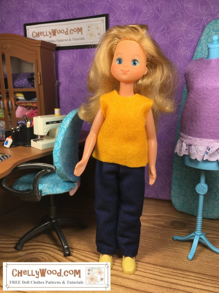 The image shows a Sunshine Family vintage female doll standing in a miniature sewing room. She wears handmade jeans and an easy-to-sew felt top. To locate the free printable PDF sewing patterns and tutorial videos for making this outfit, click on the link given in the caption for the image.