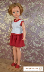 The image shows Ideal Toy Corp's Tammy Doll modeling a pair of handmade flannel shorts and a handmade flannel pajama top (sleeveless with bias tape trim) in the colors red and white. She also wears handmade slippers sewn in felt. Would you like to make these doll clothes for your vintage Tammy doll? Click on the link in the caption, and it will take you to a page where you can download and print all the free printable sewing patterns for making these doll clothes, along with links to tutorial videos that show you how to make this outfit.