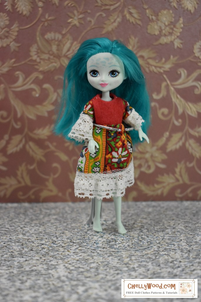 """The image shows a miniature Taylee Turtle doll wearing a handmade """"folklore"""" style of dress. The dress is made of felt, cotton, and lace trim. To download the free printable PDF sewing patterns for making this dress, and to watch the tutorial videos, please click on the link in the caption."""