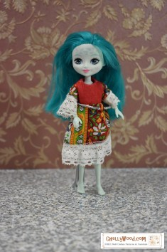 "The image shows a miniature Taylee Turtle doll wearing a handmade ""folklore"" style of dress. The dress is made of felt, cotton, and lace trim. To download the free printable PDF sewing patterns for making this dress, and to watch the tutorial videos, please click on the link in the caption."