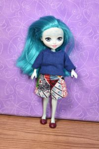 The image shows a Taylee Turtle Enchantimals doll wearing a handmade T-shirt and shorts. Please visit ChellyWood.com for free printable sewing patterns for making doll clothes to fit dolls of many shapes and all different sizes.