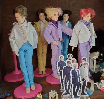 """The image shows a collection of BTS male dolls wearing jackets and pants suits in colorful fabrics. Chelly Wood's """"Ken wedding suit"""" patterns were used to make these adorable doll clothes for the BTS dolls. Special thanks to Cindy C for providing photos of her creations for followers of ChellyWood.com to enjoy and get inspiration from."""