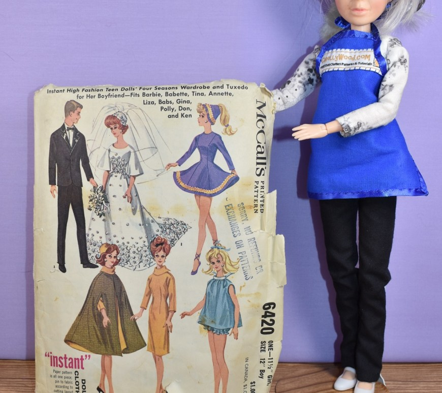 Here we see the Chelly Wood doll (she's actually a Liv doll that has had a make-over so it looks like the real person, Chelly Wood) holding up McCall's vintage Barbie pattern #6420 which has images of Barbie wearing six different outfits. The pattern's container is very worn but the images are colorful and sharp. This pattern was marked with a copyright of 1962.