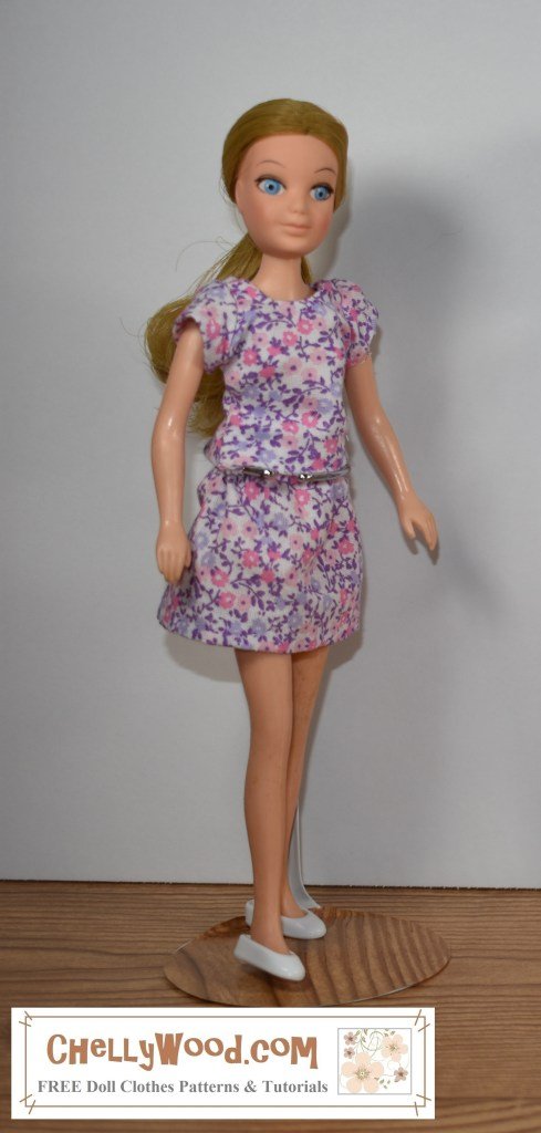 "Please click in the link provided in the caption, in order to download the free printable PDF sewing patterns and view the sewing tutorials for making this shirt and skirt doll clothes outfit for a 7-inch, 8-inch, or 9-inch doll (17 cm, 18 cm, 19 cm, 20 cm, 21 cm, or 22 cm dolls). The image here shows a ""Love"" doll from the World of Love collection of small bodied fashion dolls from Hasbro. She's wearing a handmade blouse or top with a pretty purple and pink floral print fabric. The same fabric is used to make the cute miniskirt she's wearing. The patterns and tutorials for making these doll clothes, which will fit many dolls in this size range, can be found at ChellyWood.com under 8 to 9 inch dolls => World of Love (link)."