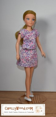 """Please click in the link provided in the caption, in order to download the free printable PDF sewing patterns and view the sewing tutorials for making this shirt and skirt doll clothes outfit for a 7-inch, 8-inch, or 9-inch doll (17 cm, 18 cm, 19 cm, 20 cm, 21 cm, or 22 cm dolls). The image here shows a """"Love"""" doll from the World of Love collection of small bodied fashion dolls from Hasbro. She's wearing a handmade blouse or top with a pretty purple and pink floral print fabric. The same fabric is used to make the cute miniskirt she's wearing. The patterns and tutorials for making these doll clothes, which will fit many dolls in this size range, can be found at ChellyWood.com under 8 to 9 inch dolls => World of Love (link)."""