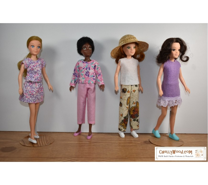 The image shows the four first World of Love dolls in handmade doll clothes that include a felt dress with eyelet trim, a long sleeve shirt, a short sleeve shirt, a sleeveless shirt, a miniskirt, a pair of ankle pants, and a pair of regular length pants. The dolls stand together on a wooden floor with a white background behind them. If you'd like to download the free printable sewing patterns for making these outfits for your 8 inch or 9 inch fashion dolls, please visit ChellyWood.com for all the free printable PDF sewing patterns and tutorial videos that you'll need to sew these doll clothes.