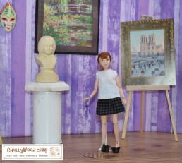 """The image shows a highly articulated Breyer Rider doll (made by the Breyer model horse company), and the doll appears to be standing in a museum filled with classical works of art, including sculpture and paintings. The doll wears a sweater (jumper in the UK) and a short houndstooth skirt with ballet flats. Please click on the link in the caption to navigate to a page where you can download and print free PDF sewing patterns for making this and other doll clothes to fit your 8"""" or 9"""" (20 cm, 21 cm, 22 cm, or 23 cm) dolls like the Breyer Riders, Bratz dolls, Stacie dolls from Mattel (Barbie's little sister), Hasbro's World of Love vintage dolls, and Mego action figures, among others."""