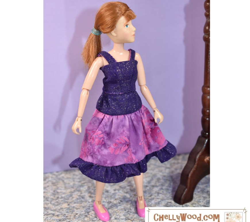 The image shows a Breyer Rider doll or action figure that stands 8 inches tall. She's wearing a handmade 3-tier skirt with a tiny ruffle along the edge of the skirt and a separate tank top made of the same purple sparkly material that the top and bottom layers of the 3-tier skirt are made of. If you'd like to sew this little doll clothes outfit for your 8-inch doll, please visit ChellyWood.com where you can download the free printable PDF sewing patterns and tutorial videos for making this skirt and top to fit 8 inch dolls.
