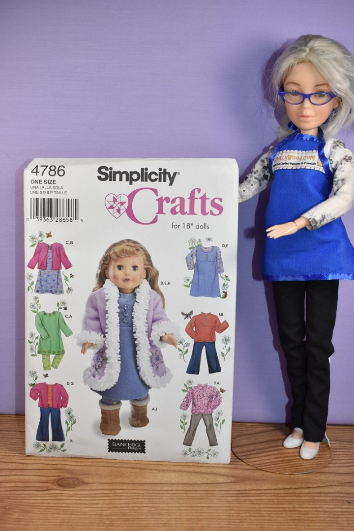 Here we see the ChellyWood doll holding up Simplicity doll clothes pattern 4786, which is particularly popular if you're looking for 18 inch doll clothes patterns for coats or jackets or winter clothing. It includes patterns for pullovers, a ski-like zip-front jacket, and a woolly long coat for winter. It also includes long sleeve shirt and jeans or pants or dungaree patterns.