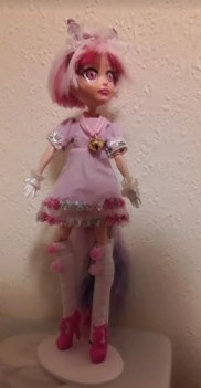 """The image shows a Monster High doll that has been modified as a """"Koneko"""" doll wearing a handmade dress by Chris W. who used Chelly Wood's St. Patrick's Day A-line dress pattern with cuffs for making this dress."""