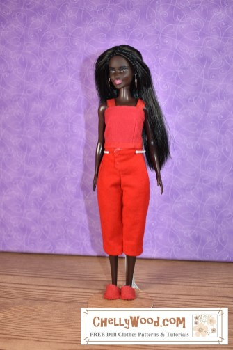 The image shows a Mattel Barbie wearing a pair of flannel capri-style pajama pants, a tank top (made of felt and ribbons), and a pair of felt slippers. The watermark tells you where you can find free printable sewing patterns for making this outfit: ChellyWood.com and if you'd like to navigate to the page where you can download the free printable PDF sewing patterns for these Barbie pajamas, please click on the link in the caption.