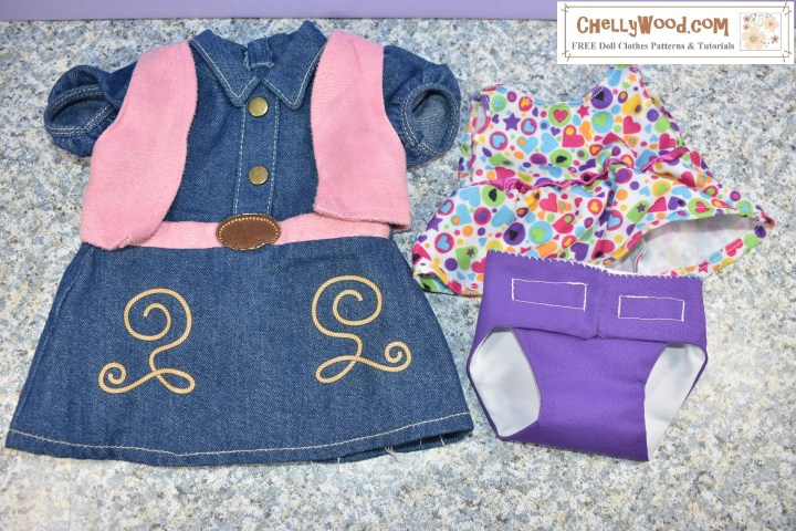 "The image shows two outfits for Baby Alive 12 inch dolls. The first one (pictured on the left) is a little denim ""cowgirl"" style dress with a pink leather-looking vest. It has tan embroidery on the skirt and a pink leather-looking belt. It has a collar and short sleeves. The second outfit consists of a multi-colored ""jumper"" style dress with hearts as part of the fabric's print and a handmade diaper that's reversible in the colors purple (on one side) and white (on the reverse side). Doll clothes designer Chelly Wood is selling these items in her eBay store, and they fit a 12 inch Baby Alive doll."