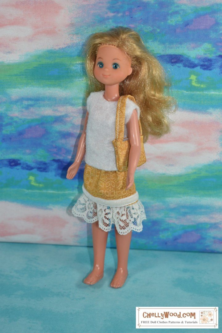 The image shows a Sunshine family doll wearing a felt sleeveless shirt, a yellow African print skirt with lace trim, and she carries a matching yellow African print handbag.