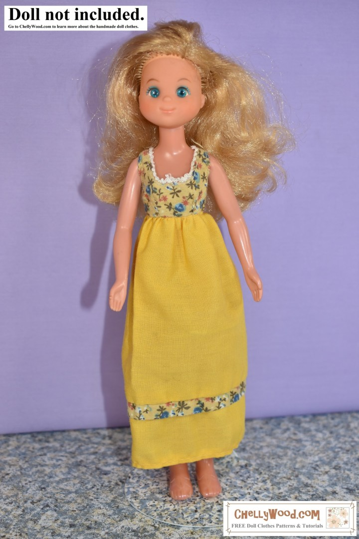 """The image shows a vintage Sunshine Family """"mom"""" doll wearing a butter yellow dress with floral bodice and floral trim. This dress is a vintage original dress, designed to be worn by a Sunshine Family female adult doll."""