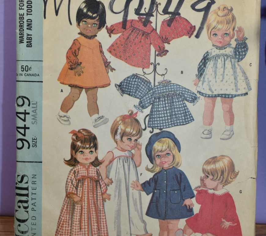 "The image shows a vintage McCall's printed sewing pattern for making a wardrobe of doll clothes for ""chubby baby and toddler dolls"" in the size range from 12 to 22 inches, depending upon whether you purchase the small, medium, or large doll clothes pattern set. The striking image on this pattern (published by McCall's in 1968) is the fact that a doll with brown skin and black hair appears on this pattern front, along with a variety of little blond and red headed dolls."
