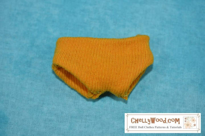 The image shows a close-up of doll underpants in yellow jersey fabric.