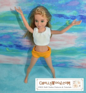 You are viewing a Mattel Stacie doll wearing a white handmade crop top and yellow handmade underpants. The doll appears to be doing jumping jacks with arms up in the air and legs spread wide.