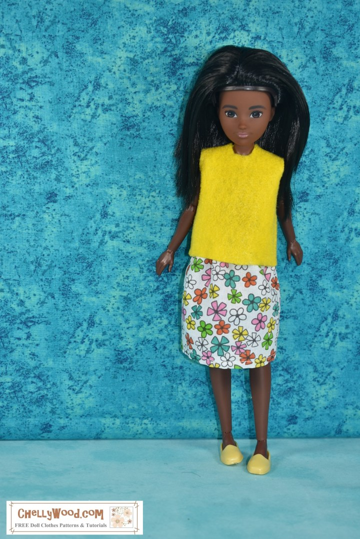 The image shows a Black Creatable World doll wearing a handmade felt skirt and an elastic-waist skirt decorated with colorful springtime flowers on a white background. The doll wears yellow loafers, and is posed elegantly with a turquoise blue background behind her.