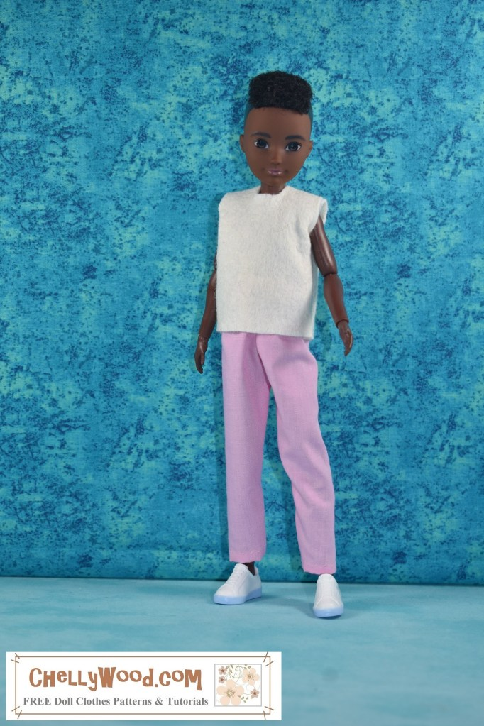 This image shows the African or African American (i.e. Black) Creatable World Doll with short hair, wearing handmade doll clothes. These doll clothes, which consist of a white felt shirt and a pair of pink ankle pants) were sewn using the free printable PDF sewing patterns from ChellyWood.com. To access Chelly Wood's free printable sewing patterns and tutorial videos for making these doll clothes for your Creatable World dolls, please click on the link in the caption.