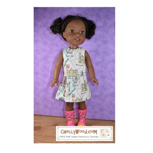 """The image shows a 14 and a half inch Wellie Wishers doll from American Girl doll company modeling a handmade doll skirt and matching shirt. The fabric used is a """"London-themed"""" printed fabric made of 100% cotton. This fabric was purchased at Hobby Lobby. If you'd like to make your own version of this outfit (a shirt and matching skirt), go to ChellyWood.com for the free printable PDF sewing patterns and the free tutorial videos showing how to make each item of doll clothes modeled here."""