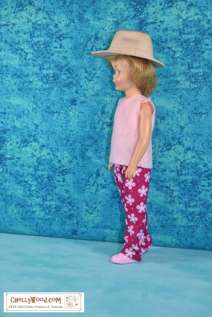 The image shows the side view of a vintage Pepper doll from the Ideal Tammy family of dolls, wearing a handmade sleeveless shirt (made of pink felt) and a pair of elastic waist pants (made of bright pink cotton with tiny pale pink flowers speckled across the fabric as a pretty and feminine print). The doll also wears a tan plastic safari-like hat (which is actually a Mattel Creatable World hat).