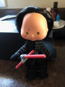 The image shows a vintage Strawberry Shortcake doll that has been customized by Sheri-Lyn S. to look like the Star Wars character Kylo Ren. It holds a tiny red light sabre and has a tiny scar across one eye. Doll clothes were handmade by Sheri-Lyn S.