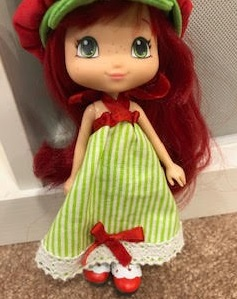 The image shows a 9-inch Strawberry Shortcake doll wearing a handmade dress that consists of green striped skirting with a lace trim and a bodice made of ribbon.