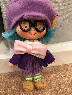 The image shows a blue-haired Strawberry Shortcake doll (possibly Blueberry Muffin) wearing doll clothes that were designed and sewn by Sheri-Lyn S. The outfit includes purple striped pants, a purple jacket, and a large pink bow tie. A purple felt hat tops the doll.
