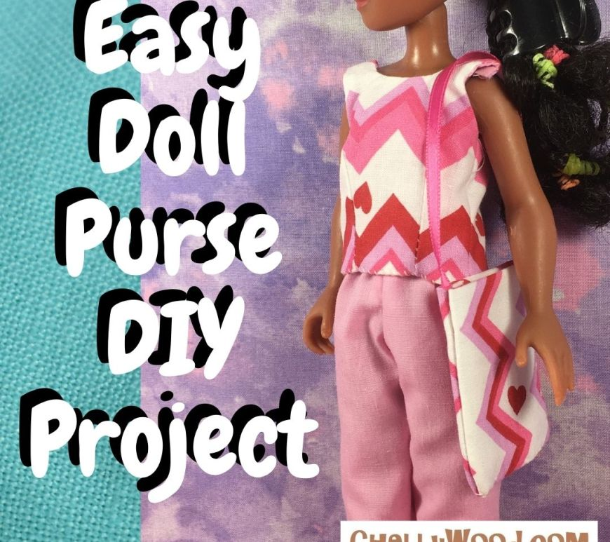 "The image shows a fashion doll holding a handmade purse. The purse is made of cotton fabric with a simple ribbon as its purse strap. The overlay says, ""easy doll purse D I Y project."" Would you like to make this super simple purse for your fashion dolls? It fits lots of dolls in sizes ranging from eight inches tall to 12 inches tall (20 centimeters to 30 and a half centimeters tall). Click on the link in the caption if you'd like to watch the video that shows you how to make this super easy doll's purse for beginners."