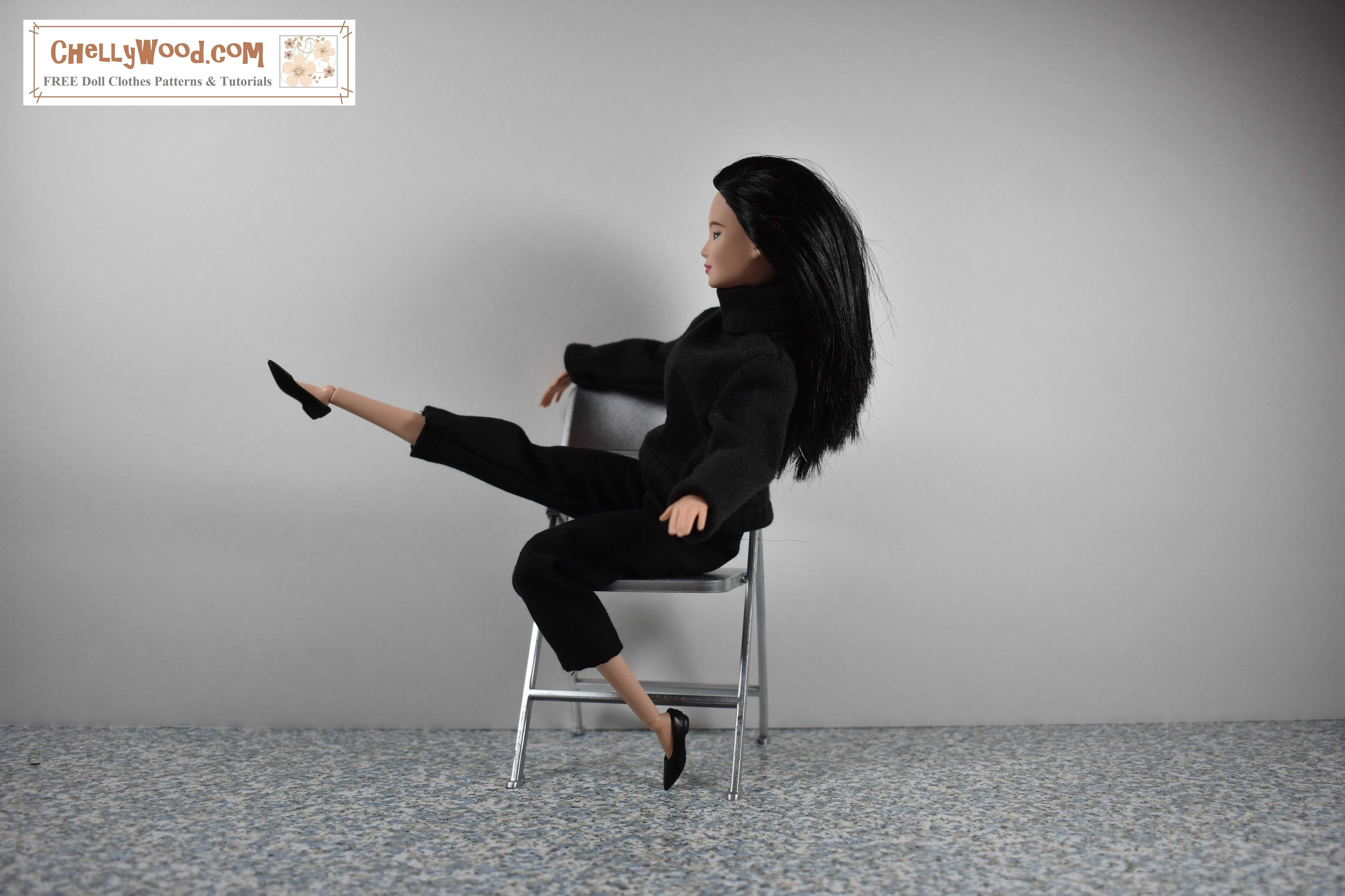 The image shows a Made-to-Move Barbie dressed like Audrey Hepburn from the early 1960's. She wears a black turtleneck with black capri pants and black plastic flats. She's seated on a tiny 1:6 scale folding chair. One arm is slung over the back of the chair, and the other arm is extended for balance. She is lifting one of her feet high into the air in front of her, while the other leg is bent with her toes just resting on a concrete floor. The wall behind her is white, creating a sharp contrast to the black clothing and silver chair. If you'd like to make this outfit, click on the link provided in the caption. You'll be taken to a page where you'll be able to download and print all the free PDF sewing patterns and watch all the free tutorial videos you'll need to make this outfit.