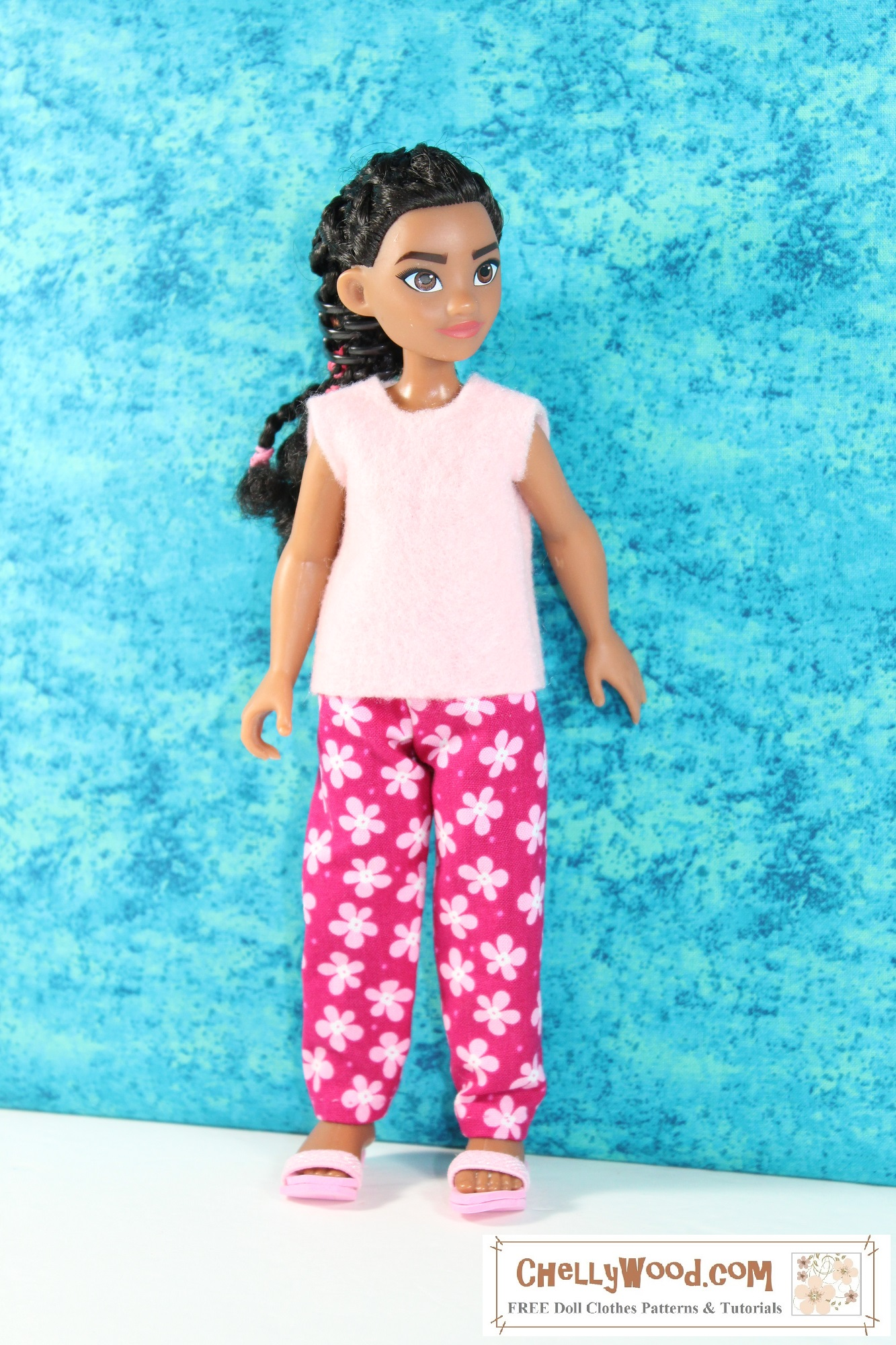 Here we see a little 10 inch Moana doll modeling handmade clothes, including a super-easy-to-sew felt shirt and a pair of elastic waist pants. The pink felt shirt coordinates nicely with the pink floral print of the pants. The little doll's hair is swept back from her face in a cascade of tiny braids, and she looks slightly to her left, avoiding the camera. She stands in front of a blue backdrop that's mottled like the Caribbean Sea. If you'd like to make this outfit for your Moana doll, please click on the link in the caption. It will take you to a page where you can find free printable PDF sewing patterns and easy-to-follow sewing tutorial videos that will help you sew this outfit, using the free printable patterns at ChellyWood.com