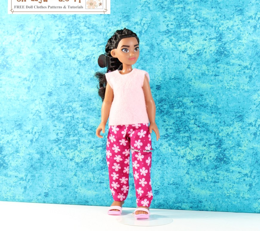 This is a photograph of a 10 inch Moana fashion doll wearing handmade doll clothes. The pink floral pants and sleeveless felt shirt Moana wears were made using free PDF sewing patterns from ChellyWood.com