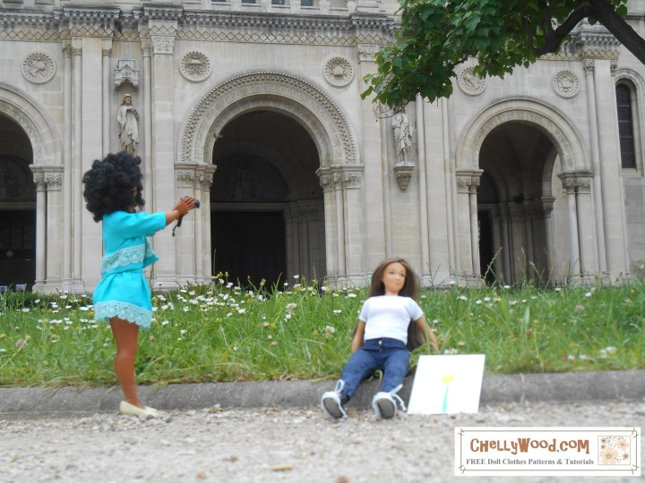 """The image shows the Lammily Photographer doll holding her camera up to take a photo of the Lammily Traveler doll, who is clearly spread-eagle and resting on some daisy-speckled grass in front of a cathedral in Paris, France. The tiny daisies look like they are exactly """"to scale"""" for these dolls, and the cathedral in the distance also seems to be """"to scale"""" for a 1:6 scale doll like the Lammily dolls. Furthermore, there is no sign of a doll stand holding the Lammily Photographer doll up. Yet she is posing quite naturally to take photo of her friend. If you'd like to learn how to make your doll's outdoor photography look so realistic and how to hide a doll stand in a photo, please visit ChellyWood.com (where this picture comes from)."""