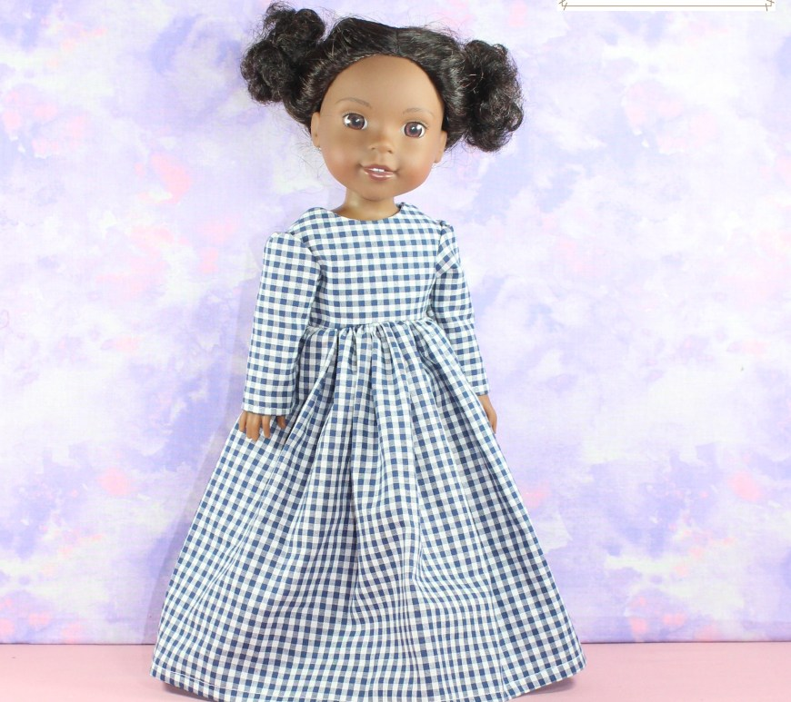 The image shows a Wellie Wishers doll modeling a beautiful, handmade Victorian-style dress. It has slightly puffed sleeves that taper to the doll's wrists. The full skirt flares a bit and gathers at the waist. The doll smiles slightly at the camera. The dress is made of blue gingham check cotton fabric, and the simplicity of the dress reminds us of the character of Laura from the Little House on the Prairie books and television show. The watermark on this image reminds us to visit ChellyWood.com for all our free printable PDF sewing patterns for making doll clothes to fit dolls of many shapes and all different sizes.