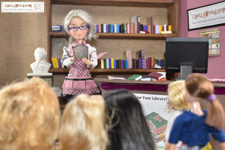 This photograph shows the Chelly Wood doll (a Spin Master Liv doll that has been repainted and had its hair dyed grey to look like the real doll clothing designer and school librarian, Chelly Wood) holding up a tiny handmade miniature book. she wears a checked librarian's apron with large pockets. She holds up a tiny book and stands before an audience of very small, child-like dolls. Behind her is a librarian's circulation with piles of books on it. Farther back in the photograph is a wall-sized (in 1:6 scale) bookshelf with dozens of colorful books on the shelf. The bookshelf appears to end at a little nook, and in the nook stands a bust of William Shakespeare (also in 1:6 scale). The watermark on the photo reminds us that this picture comes from ChellyWood.com, which offers free printable sewing patterns and tutorials for making doll clothes to fit dolls of many shapes and all different sizes.
