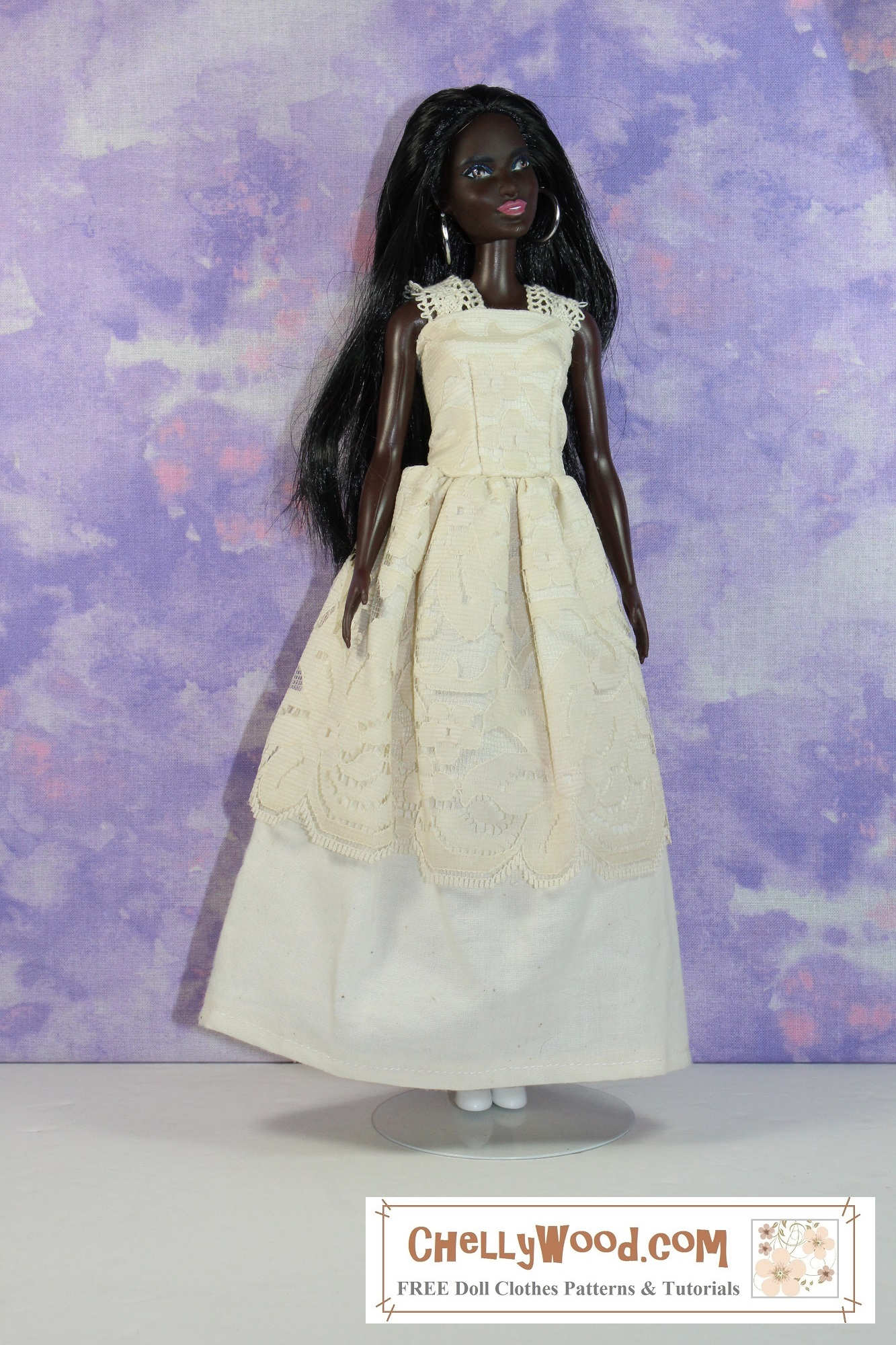 The image shows a modern Mattel Barbie doll wearing a handmade wedding gown. the bodice of the dress is overlaid with lace, and there's a layer of lace over the top of the cotton skirting. The straps of the dress are also made of lacy ribbon. The African-look Barbie has a lovely dark chocolate complexion and pink lipstick lips. Her long straight hair is worn down her back. She also wears a pair of white flats to match the cotton skirting, while the lace has more of an ivory color to it. The doll has wide hoop earrings that frame her pretty face. The doll stands on a white platform with a splotchy purple background behind her. If you'd like to download the free printable PDF sewing patterns for making this lovely wedding dress (or a less formal strappy sun dress that could also be made using this pattern) please click on the link in the caption. It will take you to the page where you can find the free printable PDF sewing patterns and the tutorial videos for making this dress.
