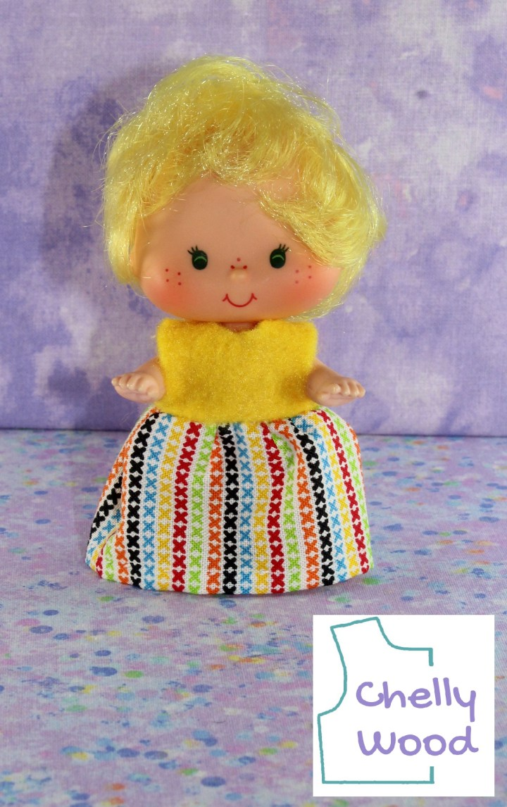 This image shows a Lemon Meringue doll from the vintage Strawberry Shortcake collection wearing a handmade dress. The bodice of the dress is bright yellow, like Lemon Meringue's curly yellow hair. It's a felt bodice, so it has a certain fluffy texture to it. The lower half of the dress--the skirt part--is made of multicolored cotton fabric. This fabric is decorated with little lines formed by aligned letter exes, in the colors blue, yellow, red, green, orange, and black on a white cotton background color. The doll stands with chubby cheeks and sparkling eyes, looking straight at the camera in anticipation. The watermark reminds us to visit ChellyWood.com for a free printable PDF sewing pattern to make this and other doll clothes to fit dolls of many shapes and sizes. Would you like the free pattern for making this miniature dress? If so, please click on the link in the caption.