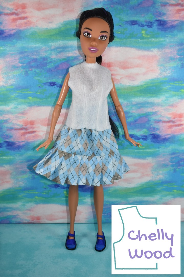 This photograph shows the 17-inch Endless Hair Kingdom Barbie modeling a handmade outfit which includes a white felt sleeveless shirt, a skirt with a pleated ruffle and elastic waist, and a pair of Mary Jane-style shoes. The doll stands before a colorful background. The overlay reminds us to visit ChellyWood.com for free printable sewing patterns. To navigate to the page where you can access the free printable PDF sewing patterns for making all of these doll clothes (including the skirt, the shirt, and the shoes), please click on the link in the caption area.