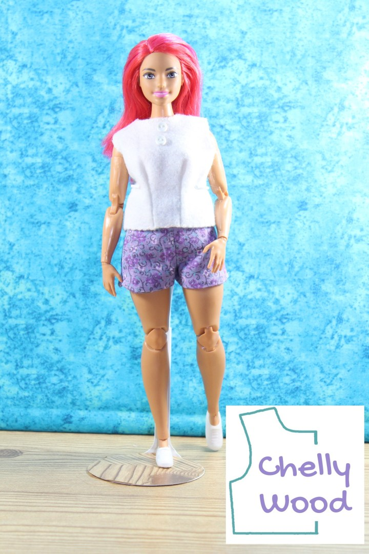 """The image shows a Made to Move Curvy Barbie with pink hair posing with one foot forward and one foot back. Her left hand rests on her thigh. Her right hand hangs loose at her side. She wears a white felt sleeveless shirt and a pair of purple floral shorts. The shirt has two tiny buttons at the top. She stands on a wood floor with a turquoise blue drape background behind her. The watermark says """"Chelly Wood"""" in purple letters, inside the turquoise outline shape of a shirt pattern."""