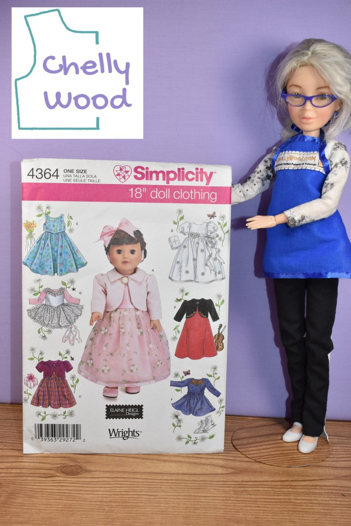 The image shows an 18 inch doll modeling a pretty pink dress on Simplicity doll clothes pattern number 4364. The pattern also displays six other dress patterns: a blue summer sundress, a pink and white tutu, a burgundy colored dress with short sleeves, a white baptismal dress, a red and black holiday dress, and an indigo-colored ice skater's dress. Beside the pattern, the Chelly Wood doll seems to be holding up the pattern for the photograph. the watermark reminds us to visit ChellyWood.com for free printable sewing patterns to fit dolls of many shapes and all different sizes.