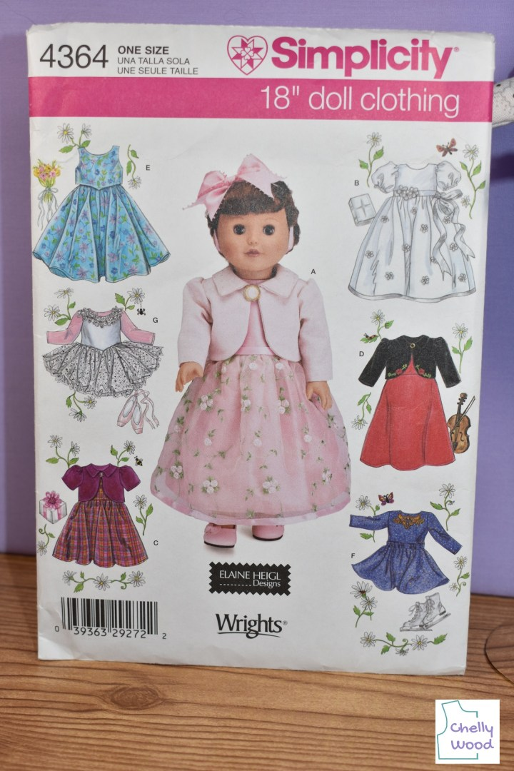 Here we see a close-up photography image of Simplicity doll clothes pattern 4364, which shows seven different styles of dresses for 18 inch dolls like American Girl, Journey Girls, etc... The pattern dresses can be described as follows: a pink dress will tulle overlay and a coat (pictured at center), a blue summer sundress, a pink and white tutu, a burgundy colored dress with short sleeves, a white baptismal dress, a red and black holiday dress, and an indigo-colored ice skater's dress. The watermark on this image reminds us that it comes from ChellyWood.com, a website offering free printable PDF sewing patterns for making doll clothes to fit dolls of many shapes and all different sizes.