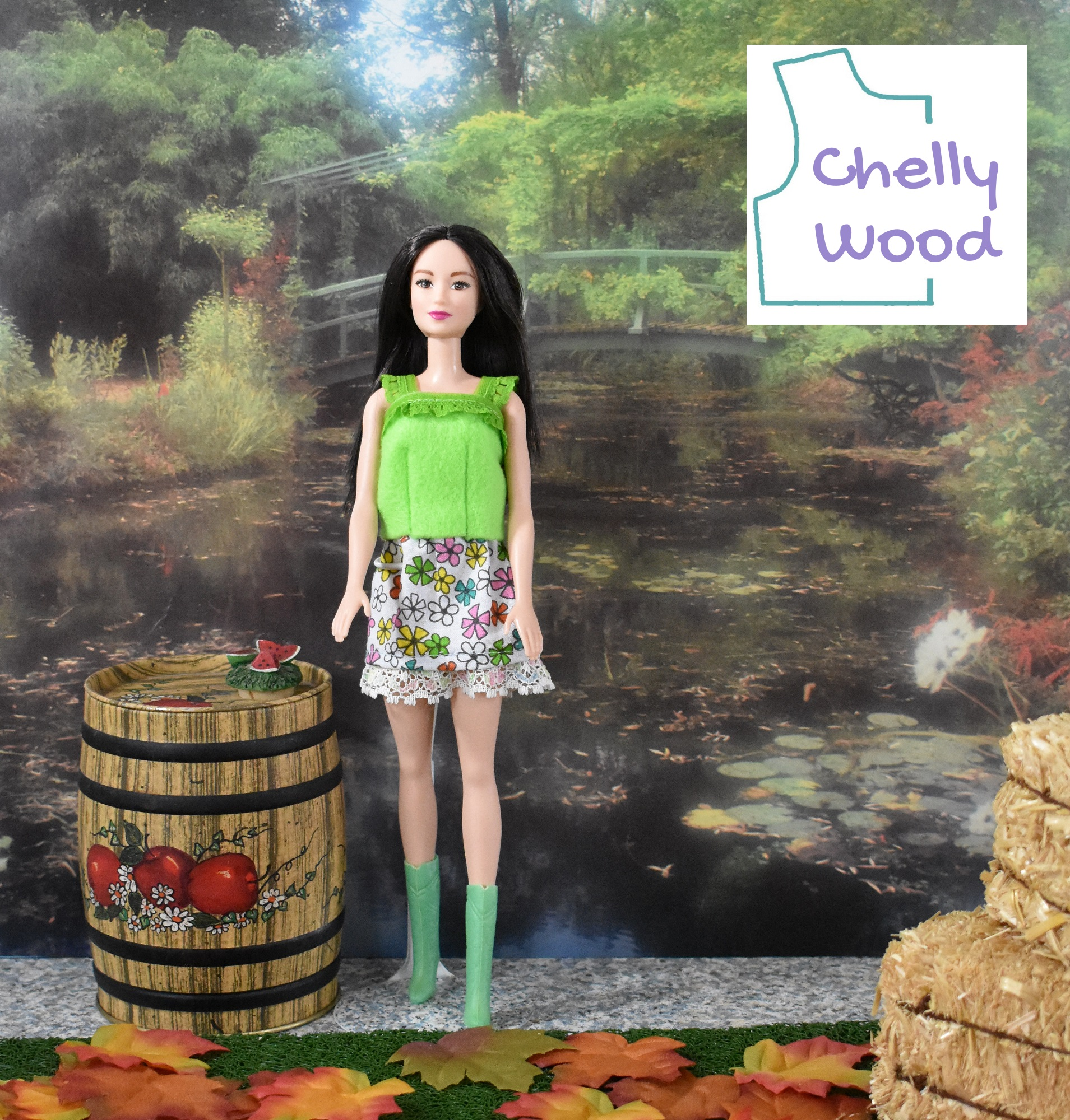 The image shows a modern Barbie modeling handmade doll clothes, including a lime green felt shirt with lace trim and lace straps along with a separate floral cotton skirt with lace trim. The doll's boots are green. She stands facing the camera. Beside her is a miniature apple barrel. If you'd like to make the outfit shown, please click on the link in the caption.